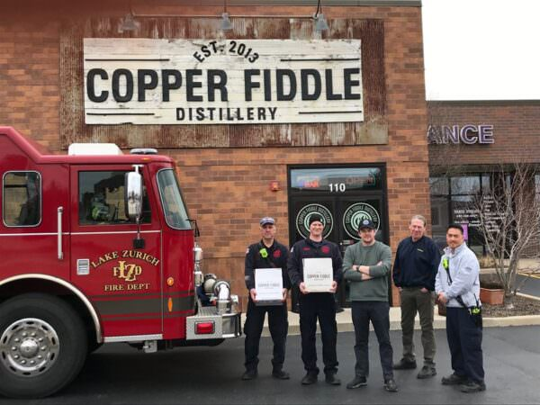 Owners of Copper Fiddle Distillery with members of the Lake Zurich Fire Department.